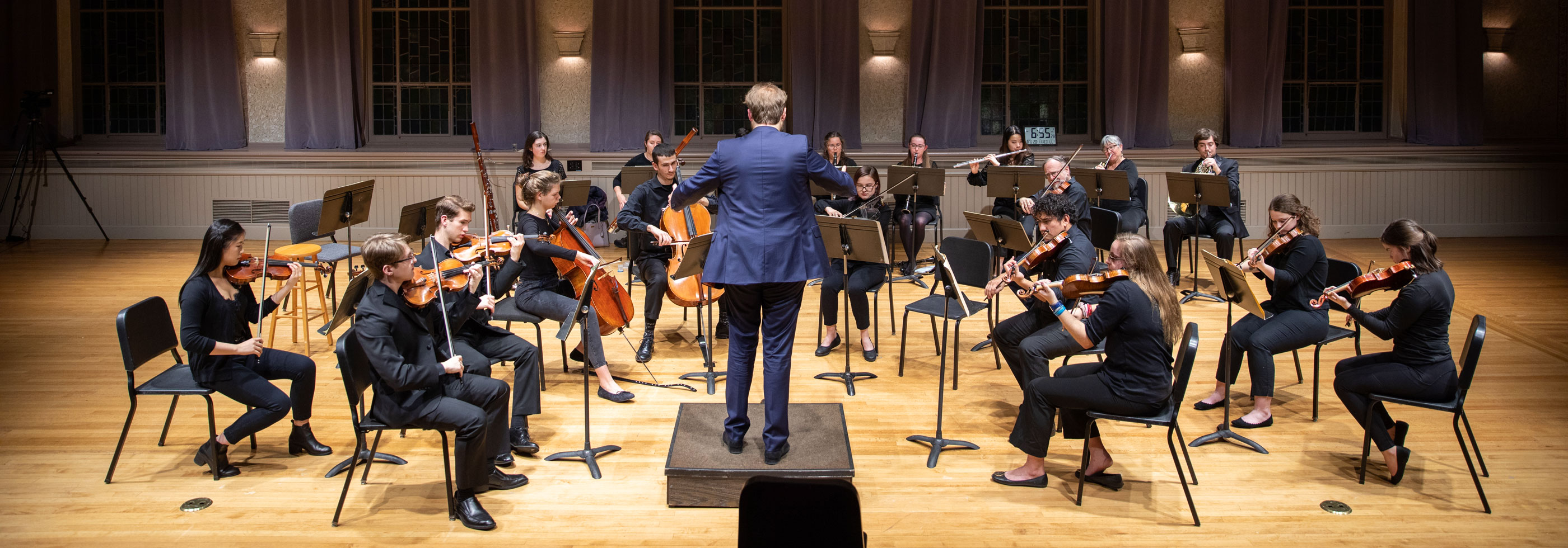 an orchestra performs with a conductor in the front