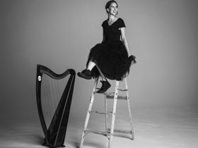 Maeve Gilchrist sitting on the top of ladder with harp on floor