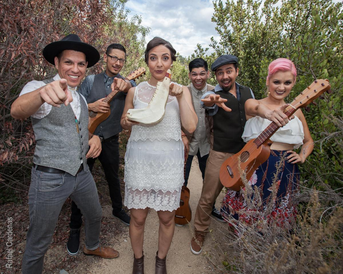 Las Cafeteras musicians point at the camera while holding instruments.