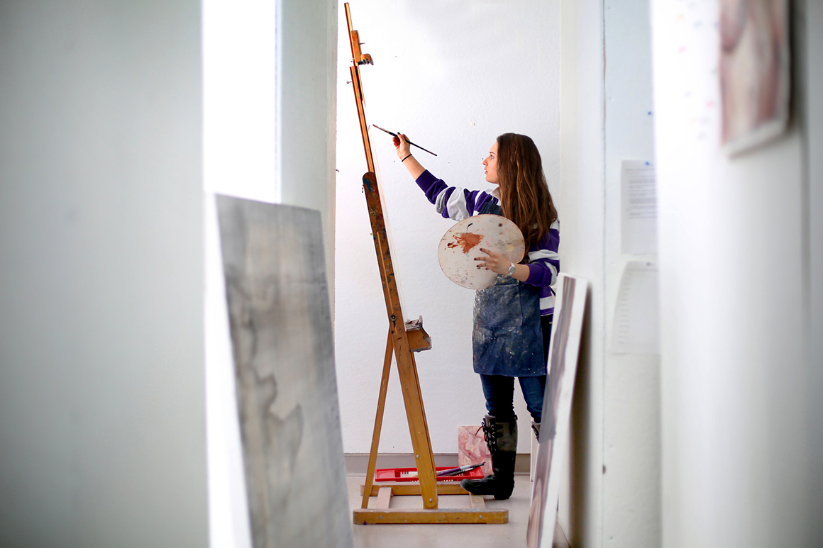 Student painting an an easel