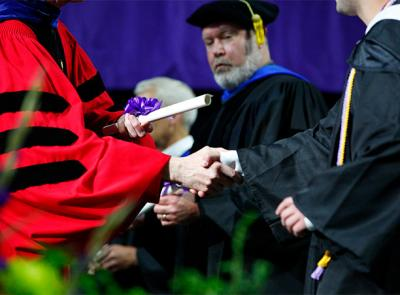 Fr. Boroughs shakes the hand of a student while handing them a diploma