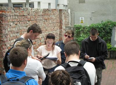 Students gather at the one of the few remaining sections of the Warsaw Ghetto Wall that was erected to seal off the Warsaw Ghetto, the largest ghetto in Poland, on a Maymester trip through central Europe.