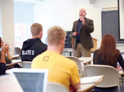 Loren Cass, dean of experiential learning and student success speaks before a class of students.