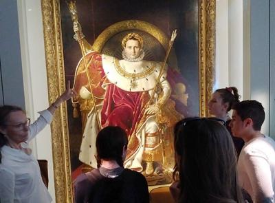 Professor Theresa McBride points out a painting to students at a museum in Paris.