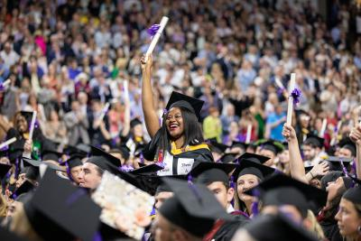 A graduating student waves her diploma at the 2019 Holy Cross graduation.