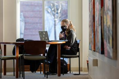 A student sits by a window on campus, working on their laptop.