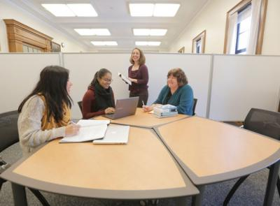 Center for Writing Director Laurie Ann Britt-Smith, far right, and Associate Director Kristina Reardon, standing, work with students on their writing