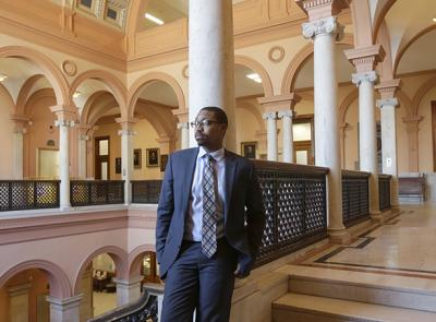 Che Anderson '11, project manager with the City of Worcester stands at Worcester City Hall. Photo by Tom Rettig