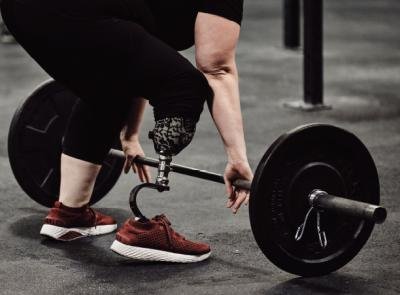 Melissa DeChellis reaches for a barbell, showing her prosthetic leg