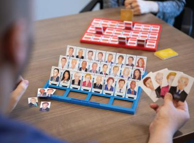 Two people play the game Guess Who where the faces have been switched for Democratic and Republican political figures