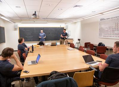 Students sit around a large table while one stands at a blackboard at the front of the room