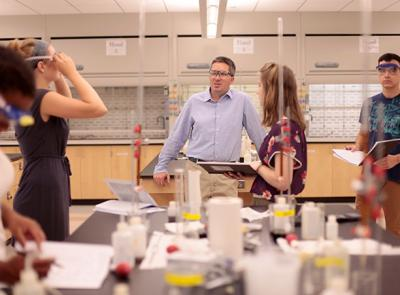 Kenneth Mills stands with students in his lab