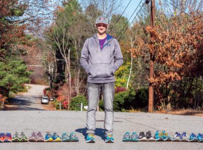 Matty Gregg stands with 31 pairs of sneakers lined up next to him