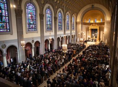 Many people stand in a very full chapel during a service