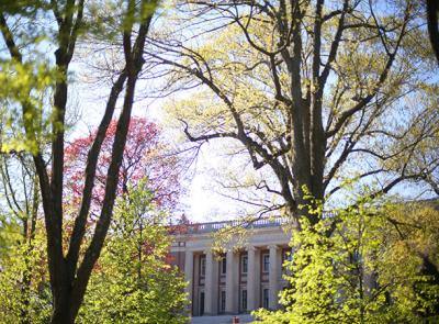 A photo of Dinand Library flanked by budding spring trees