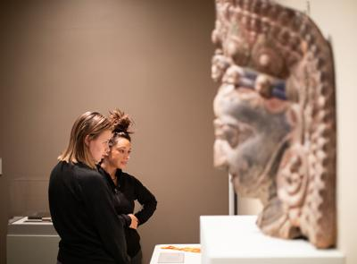 Holy Cross students are seen here admiring the objects of Buddhist devotion displayed in the Cantor Art Gallery's Dharma and Punya exhibit. Photo by Avanell Brock