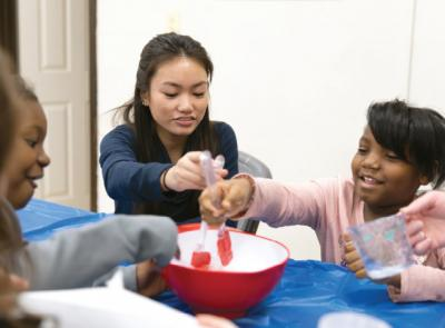 A Holy Cross student works with young students at Plumley Village