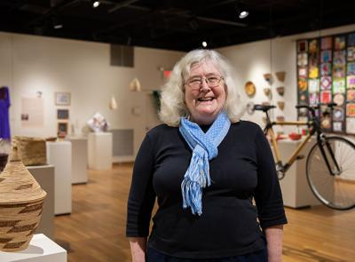 Susan Rodgers stands in an art gallery full of handmade crafts