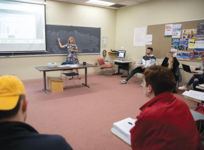 Kolleen Rask points at a blackboard in a bright classroom full of students