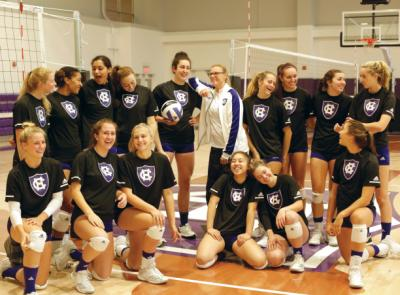 Allie Barry '19 (holding volleyball) and head coach Melissa Batie-Smoose (in white) along with this season's volleyball team in the Hart Center at the Luth Athletic Complex.