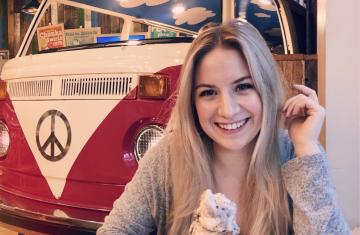 Chloe, female with blond hair, is seated at a table holding ice cream.