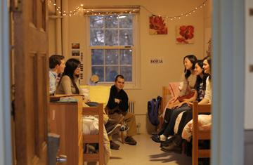 students sitting on the bed of opposite sides of a dorm room