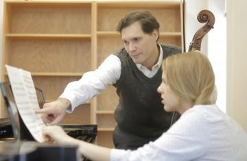 Jan with Anastasia Dulskiy at a piano looking at sheet music.