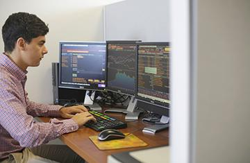student working at a desk with multiple monitors