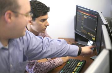 Two people looking at a computer screen on a desk