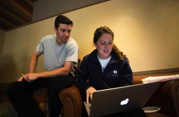 two students looking a laptop