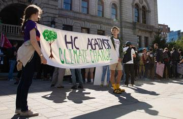 "students hold up sign that reads ""hc against climate change"" at climate strike outside worcester's city hall"