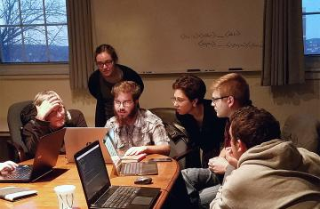 five students in a classroom looking at computer laptop