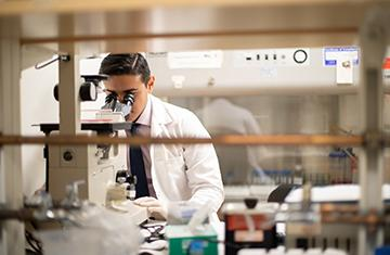 student in a lab coat looking into a microscope