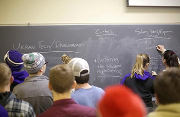 Students and faculty in a classroom at chalkboard
