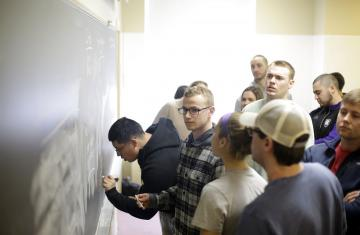 Students writing at a chalkboard