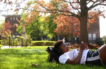 student laying on the grass