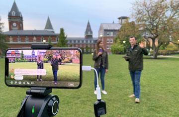students talking on grass lawn with a cameraphone in the foreground