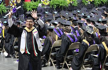Student in commencement garb holding diploma