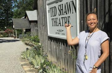 Image of Mickenzie Kamm in front of the Ted Shawn Theatre