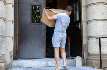 student moving a box into residence hall