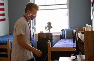student wearing mask in dorm room