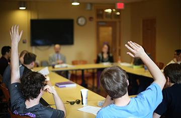 students raise their hand in a classroom