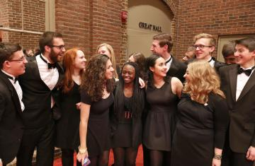 photos of about 15 chamber singers students in black