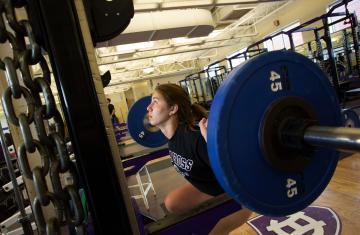 a student lifting weights in the weight room