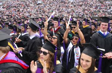 students in commencement garb waving their diplomas at commencement