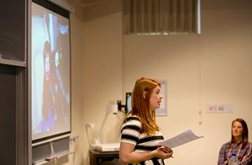 student holding a paper in front of a classroom screen