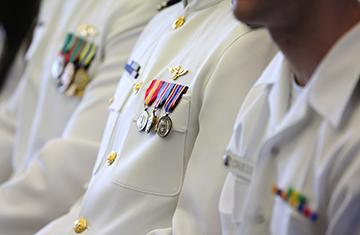 three navy officers in dress whites