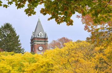O'Kane Hall clocktower flanked by fall foliage