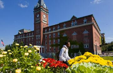 student walking by O'Kane Hall with flowers in foreground