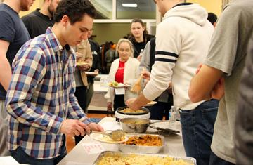 students serving pasta